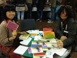 Chio and Soju stapling their zines